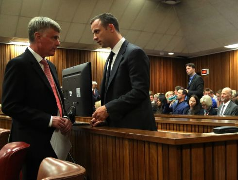 The accused speaks to an unidentified member of his legal team whilst standing in the dock. Photograph: Themba Hadebe/EPA