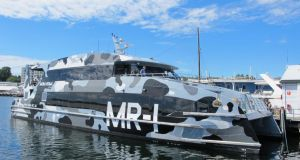 Mona Roma, a gray, camouflaged catamaran that ferries visitors to the museum
