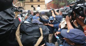 Police try to hold back the media as Carl Pistorius, the brother of Oscar Pistorius, arrives at North Gauteng High Court in Pretoria yesterday for the opening day of the athlete's murder trial. Photograph: Christopher Furlong/Getty Images