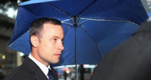 Oscar Pistorius shelters from the rain as he makes his way to North Gauteng High Court for the second day of his trial. Photograph: Christopher Furlong/Getty Images