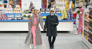 Karl Lagerfeld and model Cara Delevingne appear at the end of his autumn-winter 2014-2015 women's ready-to-wear collection for Chanel at the Grand Palais. Photograph: Stephane Mahe/Reuters