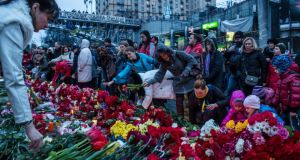 People lay flowers and pay their respects at a memorial for anti-government protesters killed in clashes with police in Independence Square in Kiev, Ukraine.  Photograph:  Brendan Hoffman/Getty Images