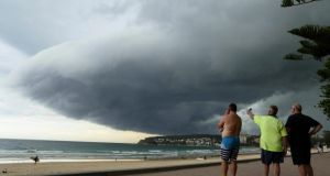 Storm clouds pass over Manly's Fairy Bower beach on Sydney's north shore as locals (L-R) Matt Fleming, Larry McMurridge and George Stantschef look on. Photograph: Will Burgess /Reuters