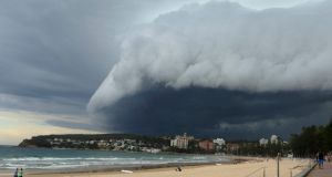 A wave-like cloud looms over Sydney's Manly Beach during an afternoon storm front. Photograph: Will Burgess /Reuters