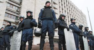 Ukrainian policemen stand guard at the Regional administration building in DonetsK. Photograph: EPA