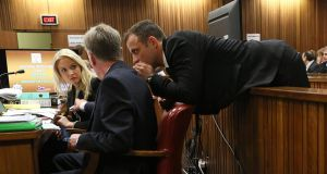 Oscar Pistorius leans over to speak to his legal counsel from the dock in court on the third day of his trial at the high court in Pretoria yesterday. Photograph: AP Photo/Alon Skuy
