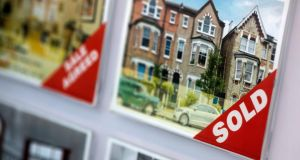 "A ""sold"" sign sits on a photograph of a residential property in an estate agent's window display in London. Photograph: Simon Dawson/Bloomberg"