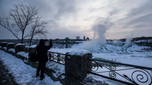 Taking photos of the big freeze. Photograph: Mark Blinch/Reuters