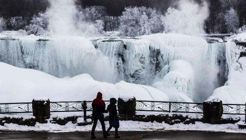 A couple looks out over the partially frozen Niagara Falls. Photograph: Mark Blinch/Reuters