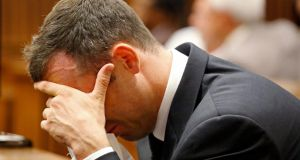 Oscar Pistorius reacts to testimony during the fifth day of his trial, for the murder of his girlfriend Reeva Steenkamp. Photograph: Schalk van Zuydam/Pool/Reuters