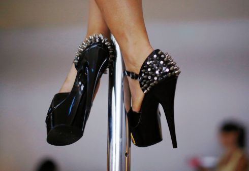 A woman wears spiked stilettos as she practises a pole dancing move during an International Women's Day event in Sydney. The event raised money for White Ribbon Australia, a campaign to stop violence against women. Photograph: Jason Reed/Reuters