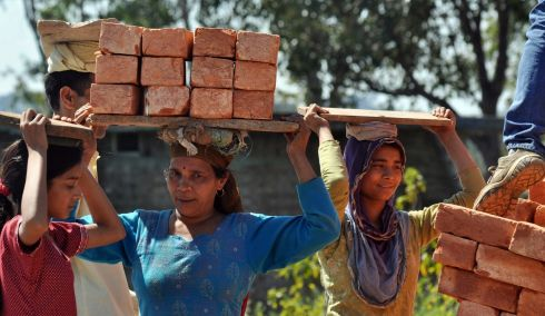 Indian daily wage female workers carry bricks on their heads as they work near a construction site in the Nagrota Bagwan village, Himachal Pradesh, India. Photograph: Sanjay Baid