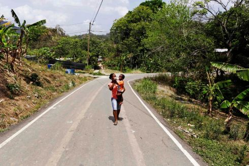 Maria Venite gives a milk bottle to her baby as she walks home in Panama City. Photograph: Carlos Jasso/Reuters