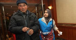 A relative (l) of a passenger of Malaysia Airlines flight MH370 is escorted by a staff member from Malaysia Airlines as they walk in a corridor at a hotel in Beijing. Photograph: Chance Chan/Reuters