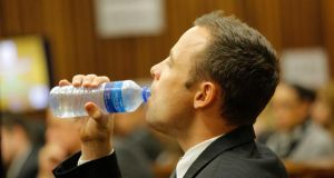South African  athlete Oscar Pistorius drinks water in the dock during his  trial for murder today in Pretoria, South Africa. Photograph: Kim Ludbrook /EPA