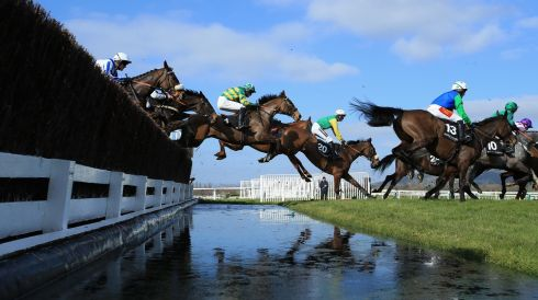 Riders in The Baylis & Harding Affordable Luxury Hanicap Steeple Chase clear the water jump.  Photograph: Richard Heathcote/Getty Images