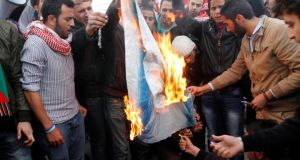 Jordanian protesters burn an Israeli flag during a protest in front of Jordanian Parliament in Amman. Photograph:  Jamal  Nasrallah/EPA