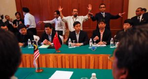 Organisers  gesture for reporters to leave a room where officials from Malaysia's Department of Civil Aviation  are meeting with members of a joint working group sent by the Chinese government to Malaysia after the disappearance of Malaysia Airlines flight MH370, at a hotel at the Kuala Lumpur International Airport today. Photograph: Damir Sagolj/Reuters