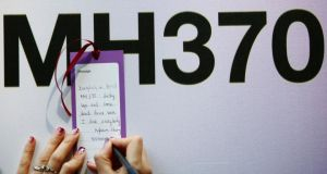 A tourist from Vietnam writes a message expressing hope for family members and those onboard the missing Malaysia Airlines flight MH370, in Kuala Lumpur today. Photograph: Samsul Said/Reuters