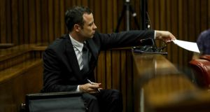Oscar Pistorius hands a note to his legal team yesterday during his murder trial at the High Court in Pretoria, South Africa. Photograph: EPA