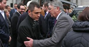 Christine Buckley's son, Darragh (left) is consoled  at her funeral. Photograph: Collins
