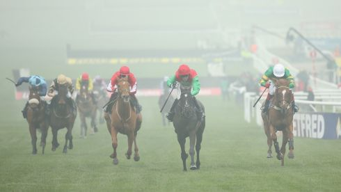 AP McCoy rides Taquin Du Seuil (centre, in red and green) to victory in the JLT Novices Chase.  Photograph: Andrew Redington/Getty Images