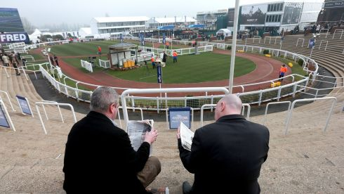 Ringside view... Racegoers check the form guides by the parade ring. Photograph: David Davies/PA