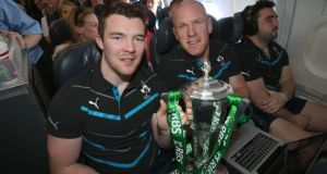 Peter O'Mahony and Paul O'Connell with the trophy on the plane on theway from Paris. Photograph: Dan Sheridan/Inpho