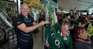 Irish rugby Fans Charlie O'Reilly and Ben Purcell from Dublin celebrate with Paul O'Connell at Dublin Airport as the squad arrive with the Six Nations Championship trophy from Paris. Photograph: Alan Betson / The Irish Times