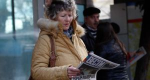 A woman reads a free newspaper with the headline 'Crimea chooses Russia' on a street in Simferopol, Crimea. Photograph: Vasily Fedosenko/Reuters