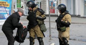 Members of a Crimean self-defence unit spot check a man's bag on a street in Simferopol today. Photograph: Stringer /Reuters