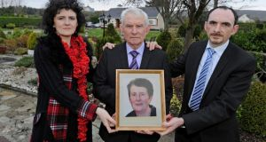 Brendan Porter with his sister Davina and their father Neil, holding a photograph of Maura Porter, who died in December. Photograph: Trevor McBride