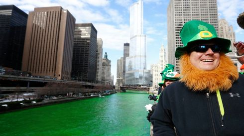 A man dressed as a leprechaun smiles as he stands beside the dyed green Chicago River during St Patrick's Day celebrations in Chicago. Photograph: Jim Young/Reuters
