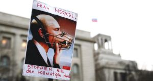 "A poster depicting Vladimir Putin with a muzzle says ""Mrs Merkel! Stop the mad dog"", seen at a demonstration outside the Russian embassy in Berlin yesterday. Photograph: Kay Nietfeld/EPA"