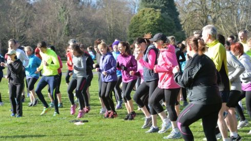 Runners warming up at the St. Annes parkrun. Warm up exercise by Mary Jennings  