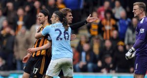 George Boyd (left) of Hull City is held back by Martin Demichelis (centre) of Manchester City after a clash with Joe Hart (right)  at the KC Stadium. Photograph:  Clint Hughes/Getty Images