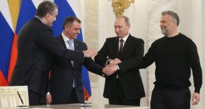 Russia's president Vladimir Putin (2nd right) shakes hands with (left to right) the head of Crimea's government Sergei Aksionov, chairman of Crimean parliament Vladimir Konstantinov and head of Sevastopol city administration Alexei Chaliy after signing the treaty on incorporation of Crimea with Russia at the Grand Kremlin Palace in Moscow. Photograph: Ekaterina Shtukina/EPA.