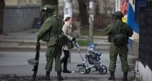 A woman and her child walk past soldiers without insignia as they stand guard outside a Ukrainian military base in Simferopol today. Photograph: Uriel Sinai/The New York Times.