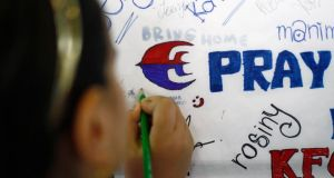 A child leaves a message of support for family members and passengers onboard the missing Malaysia Airlines Flight MH370 at  Kuala Lumpur International Airport. Photograph:   Samsul Said/Reuters