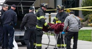 Authorities remove a body from the wreckage of a KOMO News helicopter which crashed near the Space Needle in Seattle. Photograph: David Ryder/Reuters.