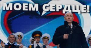 "'When it comes to double-talk, however, there is no contest. Putin is never going to be a match for Obama at talking out of both sides of his mouth at the same time.' Above, Vladimir Putin addresses the  audience during a rally and a concert called ""We are together"" to support the annexation of  Crimea, on March 18th. The words in the background read, ""Crimea is in my heart"". Photograph: Maxim Shemetov/Reuters"