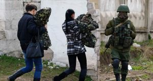 Two women, believed to be Ukrainian servicewomen, carry their uniforms as they walk past an armed man, believed to be a Russian serviceman, while leaving a military base in Perevalnoye, near the Crimean city of Simferopol, March 19, 2014. Ukraine's National Security and Defence Council opened a session on Wednesday devoted to threats to national security following Russia's moves to take control of the Crimea peninsula. REUTERS/Shamil Zhumatov