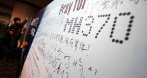 Family members of passengers onboard the missing Malaysian Airlines flight MH370 write messages to their missing relative on a board at a hotel in Beijing today. Photograph: Kim Kyung-Hoon/Reuters