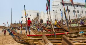 Cape Coast Castle, with its chilling slave dungeons, behind traditional fishing boats. Photographs: Getty