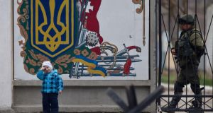 A child pauses by the emblem of a Ukrainian military base as a pro-Russian soldier walks behind the main gate in Perevalne, Crimea. photograph: vadim ghirda/ap