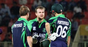 Ireland's Paul Stirling with physio Andrew Dunne and captain William Porterfield after picking up an injury against UAE. Photograph: Barry Chambers/Inpho