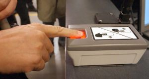 "An arriving passenger at John F. Kennedy International Airport  uses a machine that takes inkless fingerprints. Scientists are developing tiny wires to be used to produce ""nanoscale fingerprints"" that are invisible to the human eye."