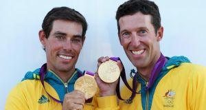 Mat Belcher (left) shows the Olympic gold medal he won in the men's 470 sailing event at London 2012. The Australian has now signed up to skipper the Australian challenger in the next America's Cup. Photograph: Clive Mason/Getty Images