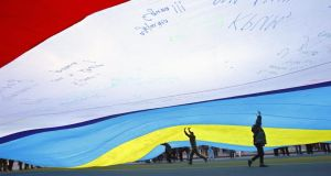 Ukrainian youngsters run under a huge composite flag (Ukrainian and Crimean flags) containing thousands of signatures and being carried by a crowd in  Independence Square,  Kiev, yesterday. Photograph: Robert Ghement/EPA
