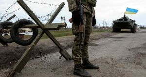 A Ukrainian soldier  guards a checkpoint near the village of Salkovo, in the Kherson region adjacent to Crimea. Photograph: Valentyn Ogirenko/Reuters